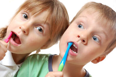 Pictureof two children brushing their teeth, a blonde girl with a pink toothbrush and a blonde boy with a blue toothbrush